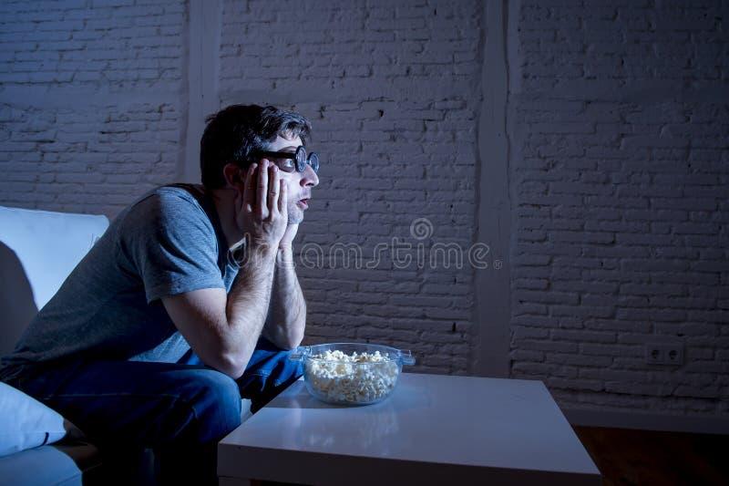 Hombre del adicto a la televisión en el sofá que ve la TV y que come las palomitas en vidrios divertidos del friki del empollón foto de archivo