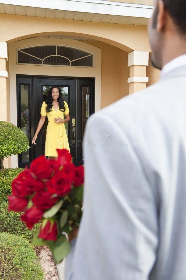 Hombre del afroamericano que trae las flores a la esposa imágenes de archivo libres de regalías