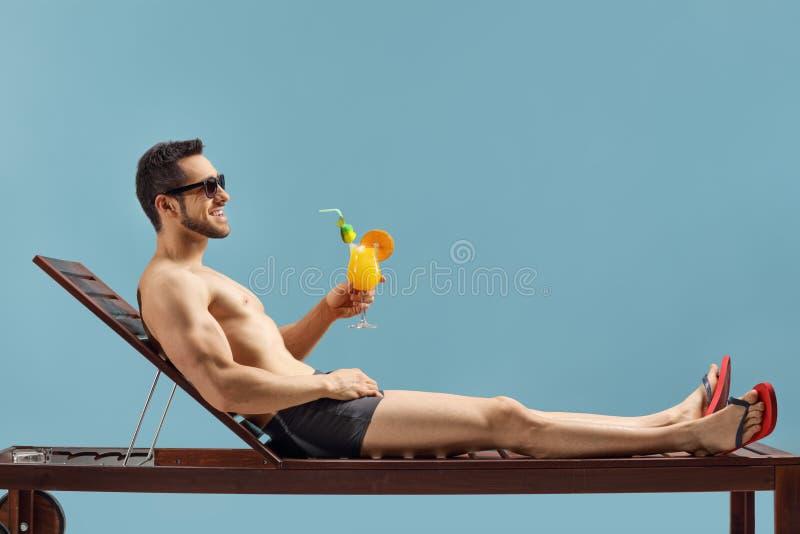 Hombre del ajuste que goza de un cóctel en sunbed foto de archivo libre de regalías