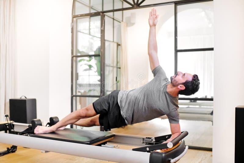 Hombre del ajuste que hace ejercicios laterales del tablón del codo de los pilates foto de archivo
