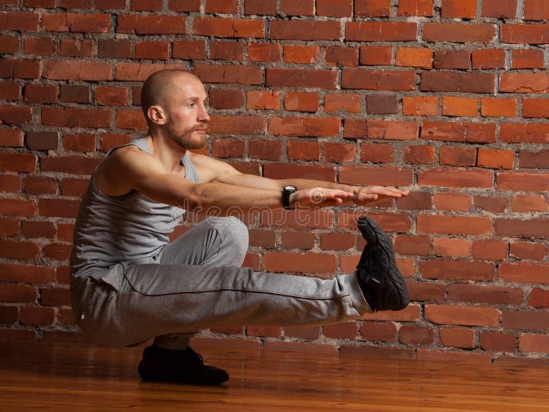 Hombre del atleta que realiza posición en cuclillas en una pierna foto de archivo libre de regalías