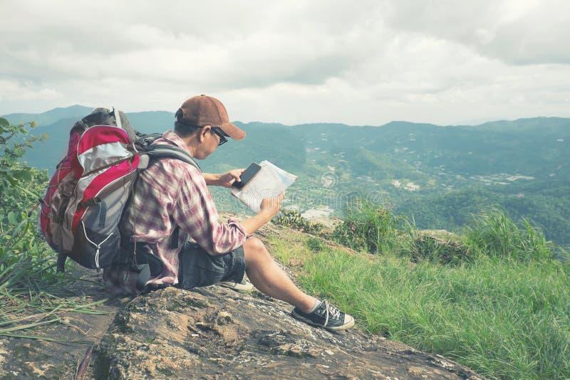 Hombre del Backpacker que busca la dirección correcta en mapa imagenes de archivo