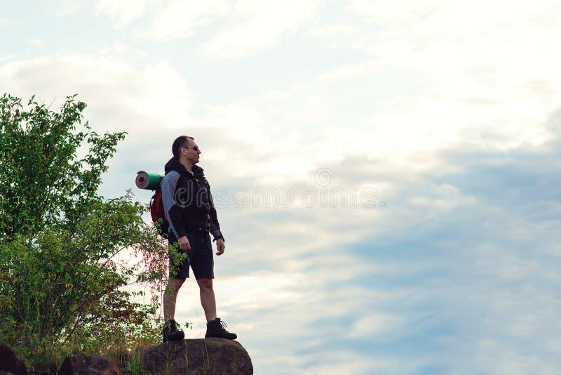 Hombre del caminante con la mochila que se coloca encima de la montaña foto de archivo libre de regalías