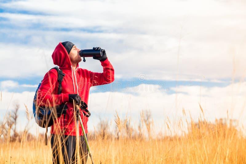 Hombre del caminante en el agua potable del campo de la botella de agua imágenes de archivo libres de regalías