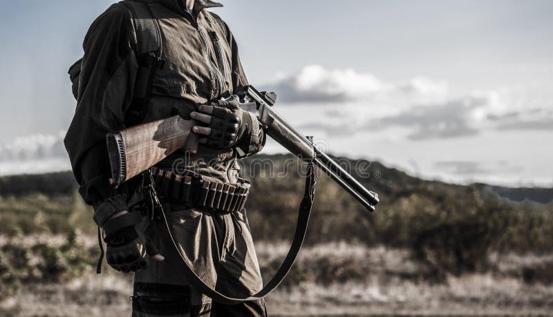 Hombre del cazador Búsqueda de período, estación del otoño Varón con un arma Cazador con una mochila y un arma de búsqueda Un caz foto de archivo libre de regalías