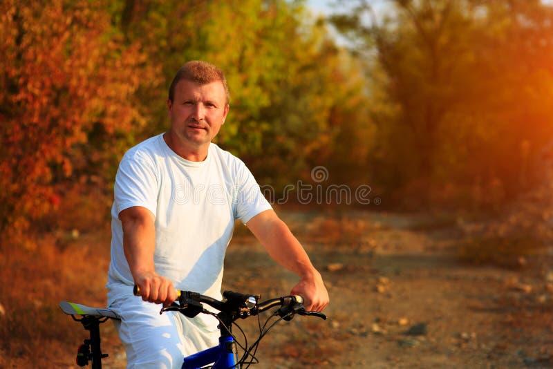 Hombre del ciclista que completa un ciclo en un camino rural durante puesta del sol imagen de archivo