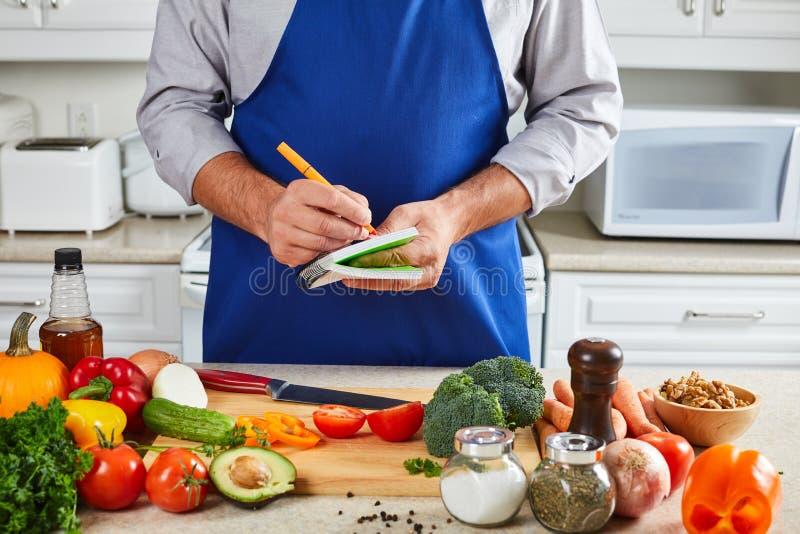 Hombre del cocinero que cocina en la cocina fotos de archivo