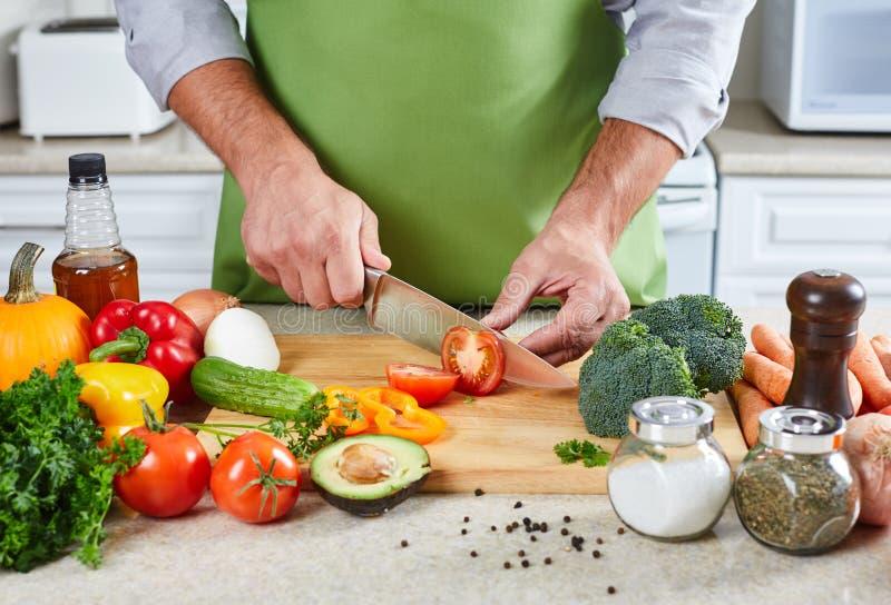 Hombre del cocinero que cocina en la cocina imagen de archivo