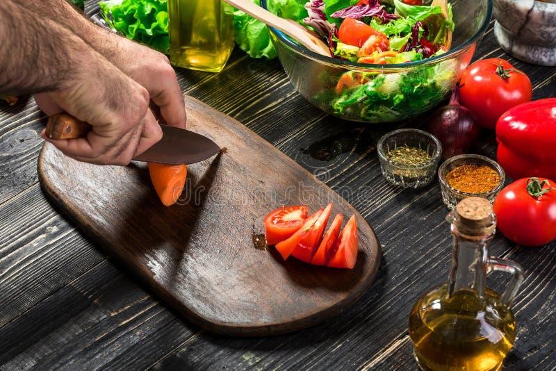 Hombre del cocinero que cocina en la cocina La mano del ` s del hombre corta la zanahoria en un tablero de madera foto de archivo