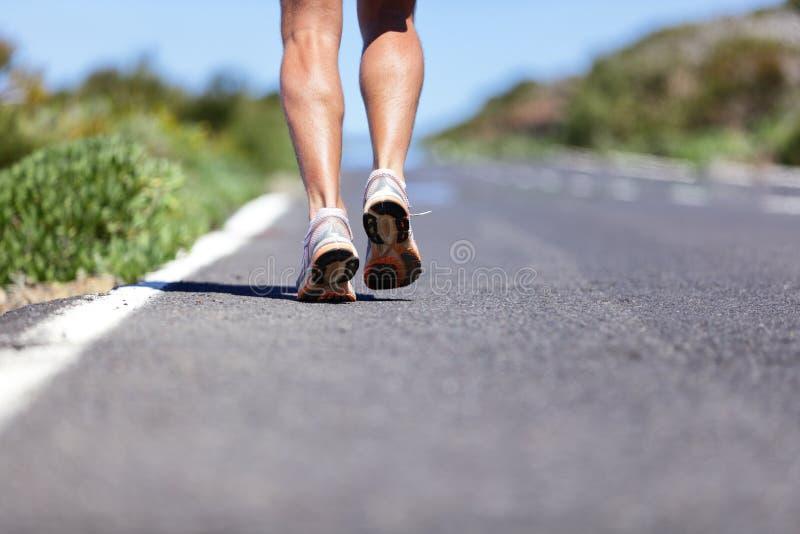 Hombre del corredor con las zapatillas deportivas en el camino al éxito imagenes de archivo
