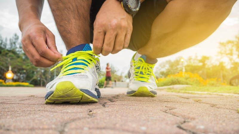 Hombre del corredor que ata los cordones de zapatillas deportivas que consiguen listos fotos de archivo libres de regalías
