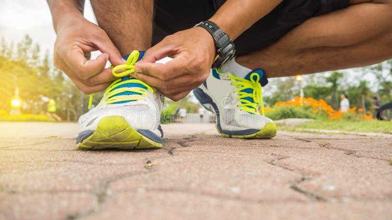 Hombre del corredor que ata los cordones de zapatillas deportivas que consiguen listos para la raza imágenes de archivo libres de regalías