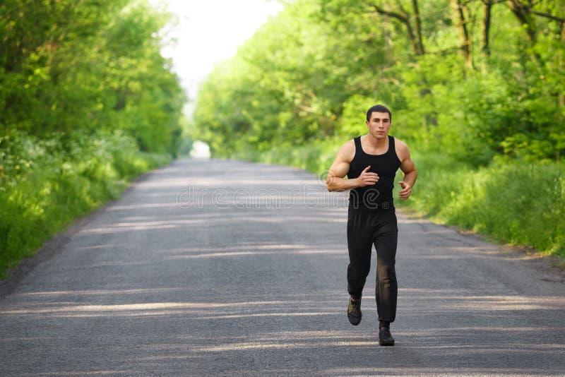Hombre del corredor que corre en sprint del entrenamiento del camino Elaboración corrida varón que se divierte afuera imagen de archivo