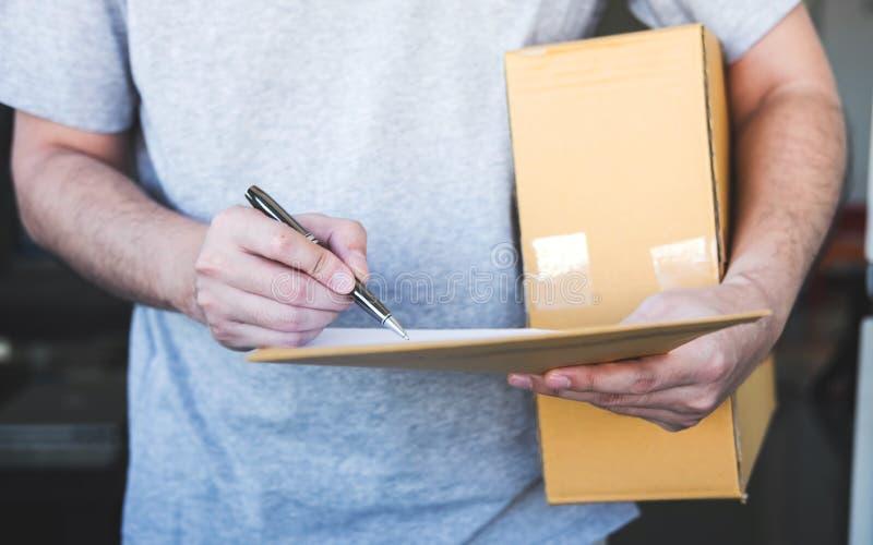 Hombre del correo de la entrega que da la caja del paquete a la forma del beneficiario y de la firma, recibo de firma del dueño j imagen de archivo