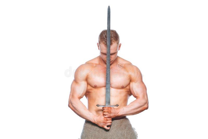 Hombre del culturista que presenta con una espada aislada en el fondo blanco Hombre descamisado serio que demuestra su cuerpo mas foto de archivo libre de regalías