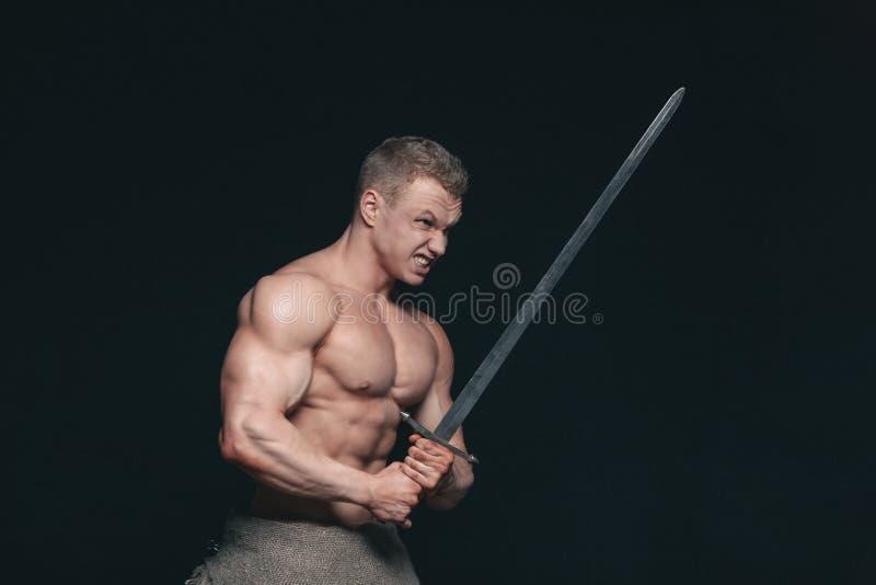 Hombre del culturista que presenta con una espada aislada en fondo negro Hombre descamisado serio que demuestra su cuerpo mascula fotos de archivo libres de regalías