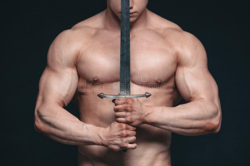 Hombre del culturista que presenta con una espada aislada en fondo negro Hombre descamisado serio que demuestra su cuerpo mascula imagen de archivo