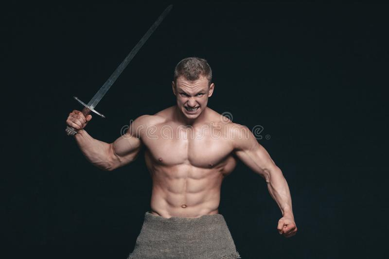 Hombre del culturista que presenta con una espada aislada en fondo negro Hombre descamisado serio que demuestra su cuerpo mascula imagenes de archivo