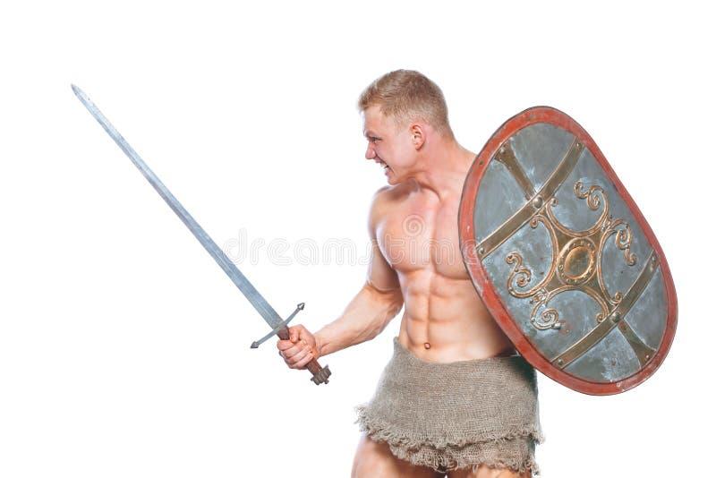 Hombre del culturista que presenta con una espada y un escudo aislados en el fondo blanco Hombre descamisado serio que demuestra  foto de archivo libre de regalías