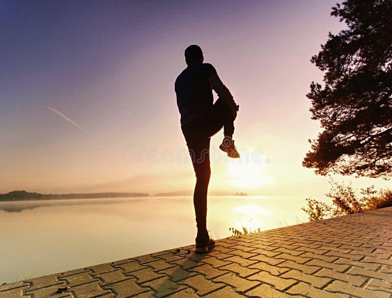 Hombre del deporte atlético que estira los músculos de la pierna antes de funcionamiento fotos de archivo