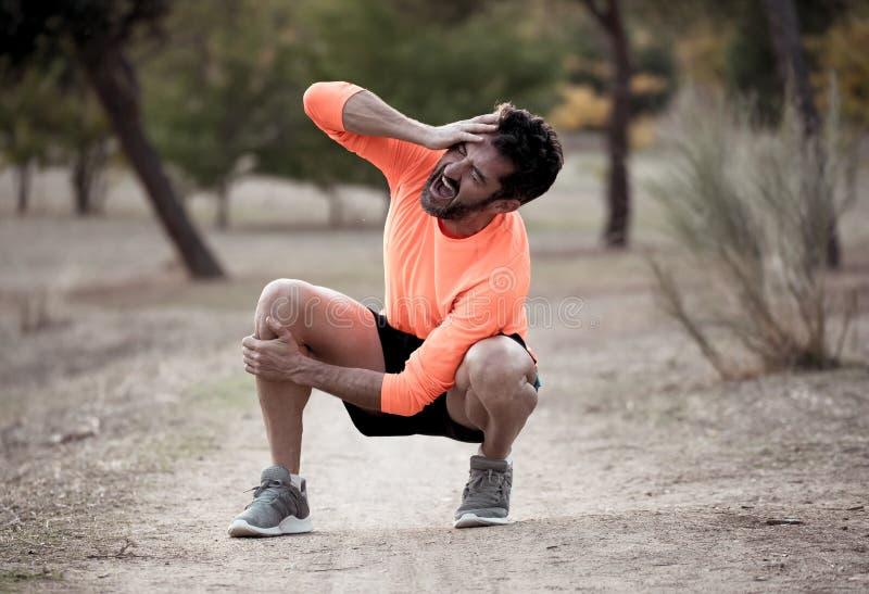 Hombre del deporte herido al ejercitar o corriendo sosteniendo su rodilla que grita en dolor foto de archivo libre de regalías