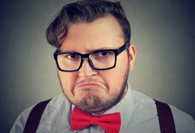 Hombre del descontento en lentes en gris fotografía de archivo