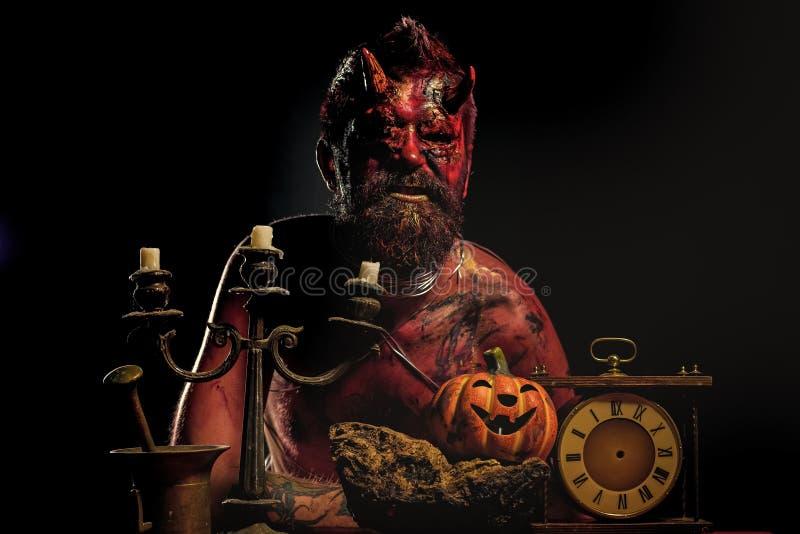 Hombre del diablo de Halloween con la calabaza, reloj, palmatoria en la tabla foto de archivo libre de regalías