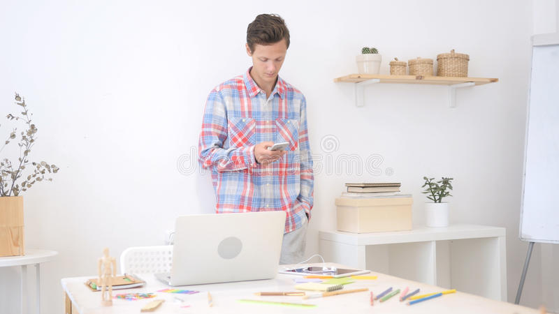 Hombre del diseñador que usa smartphone en la oficina del creatve que envía el mensaje en medios sociales foto de archivo libre de regalías