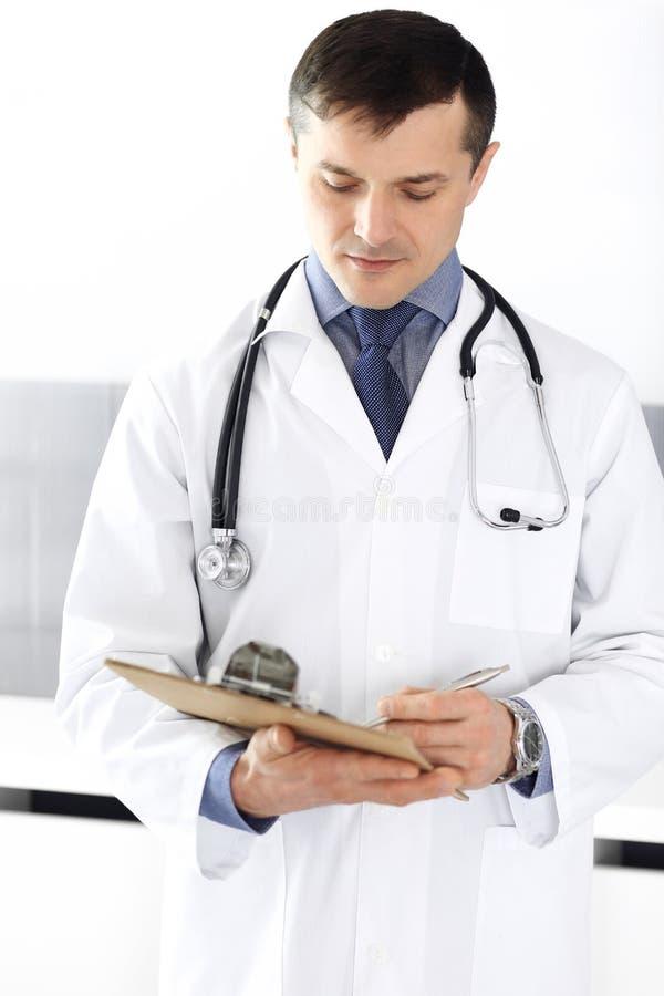 Hombre del doctor usando el tablero para llenar encima de expedientes de historia de medicaci?n Servicio m?dico perfecto en cl?ni foto de archivo
