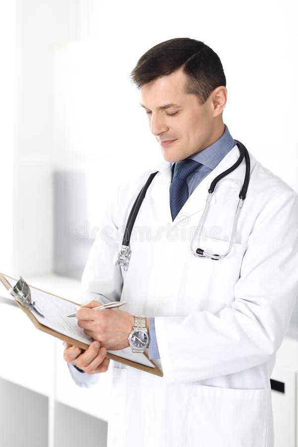 Hombre del doctor usando el tablero para llenar encima de expedientes de historia de medicaci?n Servicio m?dico perfecto en cl?ni fotos de archivo