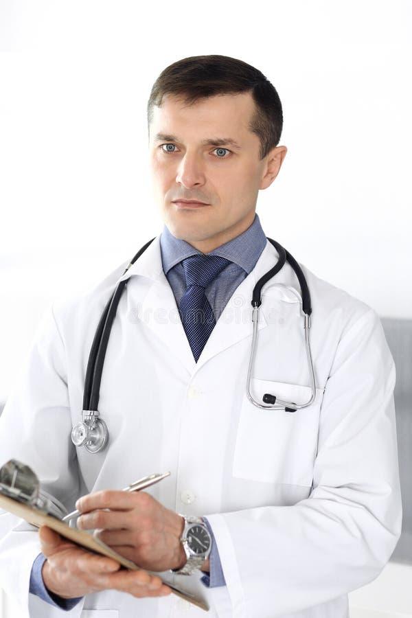 Hombre del doctor usando el tablero para llenar encima de expedientes de historia de medicaci?n Servicio m?dico perfecto en cl?ni imagen de archivo libre de regalías