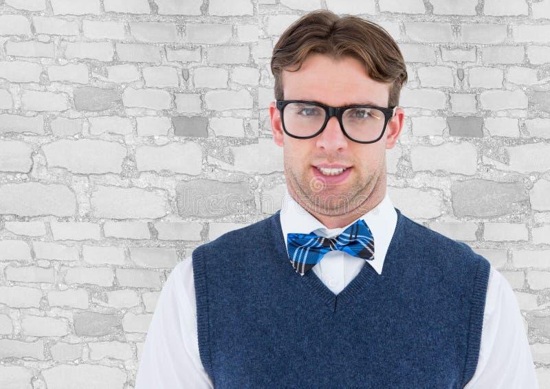 Hombre del empollón en chaleco azul contra la pared de ladrillo blanca imagen de archivo