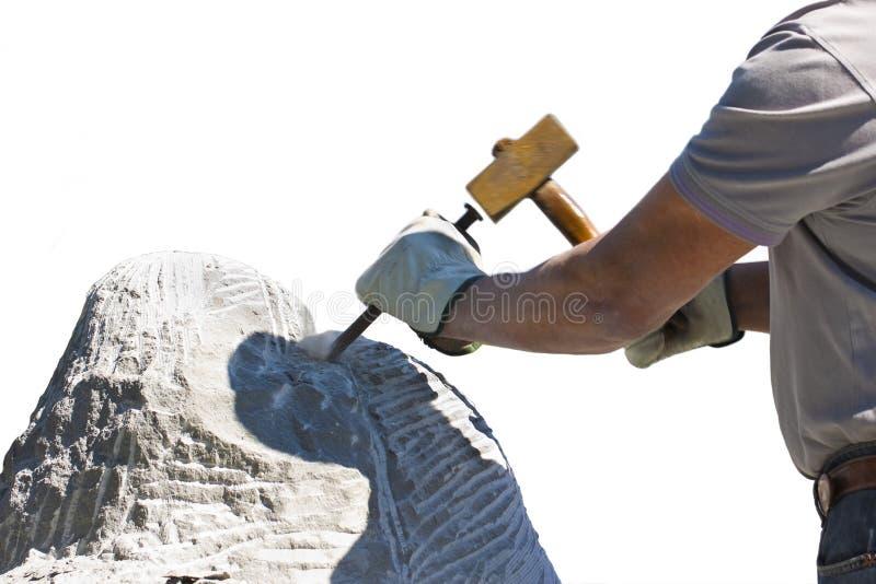 Hombre del escultor en el trabajo con el martillo y guantes protectores a tallar un bloque de piedra en el fondo blanco para la s fotografía de archivo