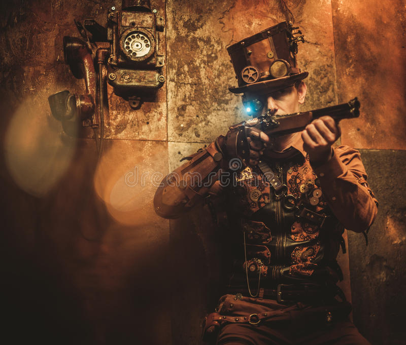 Hombre del estilo de Steampunk con los diversos dispositivos mecánicos en fondo del steampunk del vintage imagenes de archivo