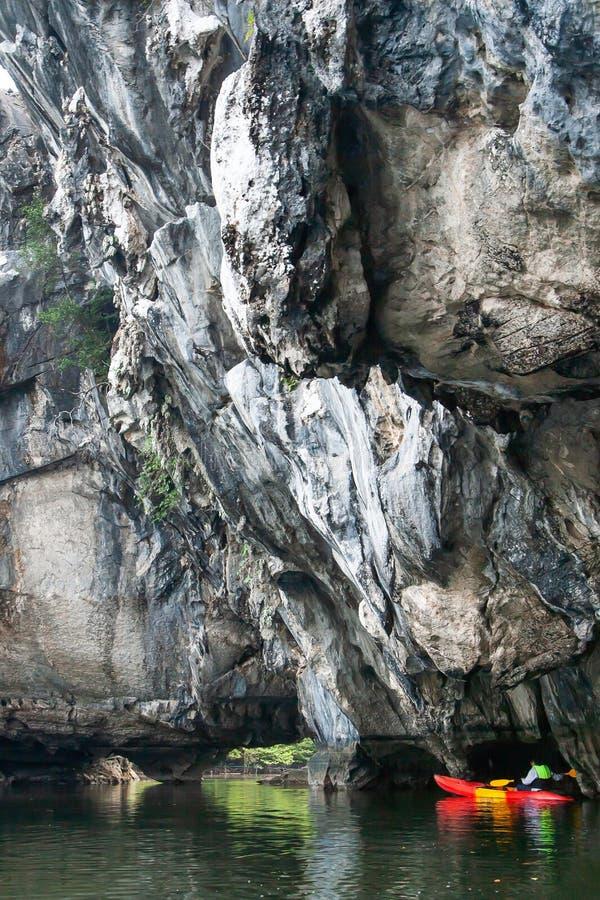 Hombre del explorador en chaleco salvavidas kayaking delante del acantilado escarpado de la piedra caliza en el mar imagen de archivo