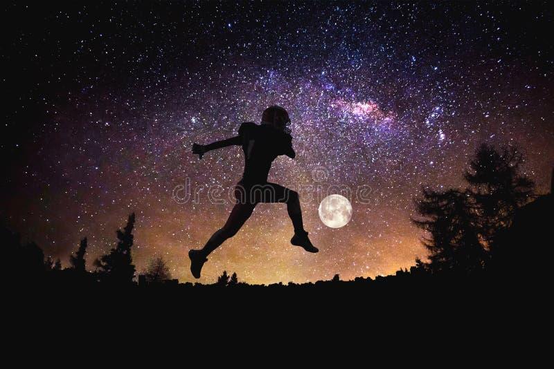 Hombre del fútbol del jugador que salta en el fondo estrellado del cielo de la noche Técnicas mixtas foto de archivo libre de regalías
