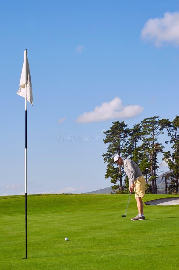 Hombre del golf que pone en verde imagenes de archivo