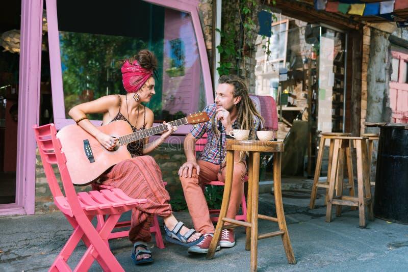 Hombre del hippie que escucha su novia que juega música imagen de archivo