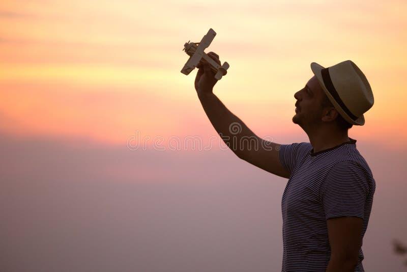 Hombre del inconformista con el sombrero que sostiene el pequeño aeroplano de madera retro al aire libre foto de archivo