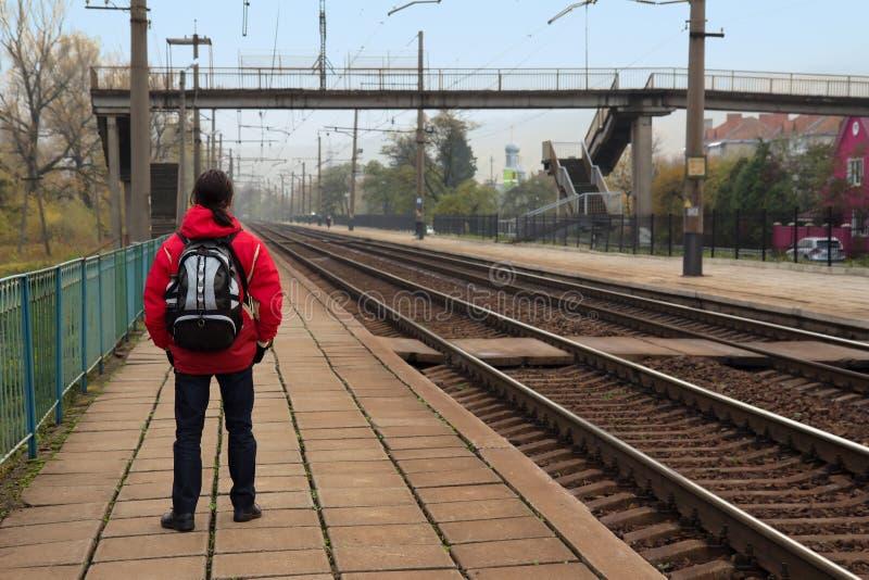 Hombre del inconformista con la mochila que espera un tren en la plataforma ferroviaria fotos de archivo