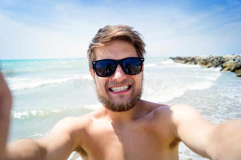 Hombre del inconformista en la playa, sonrisa, tomando el selfie, verano soleado fotos de archivo