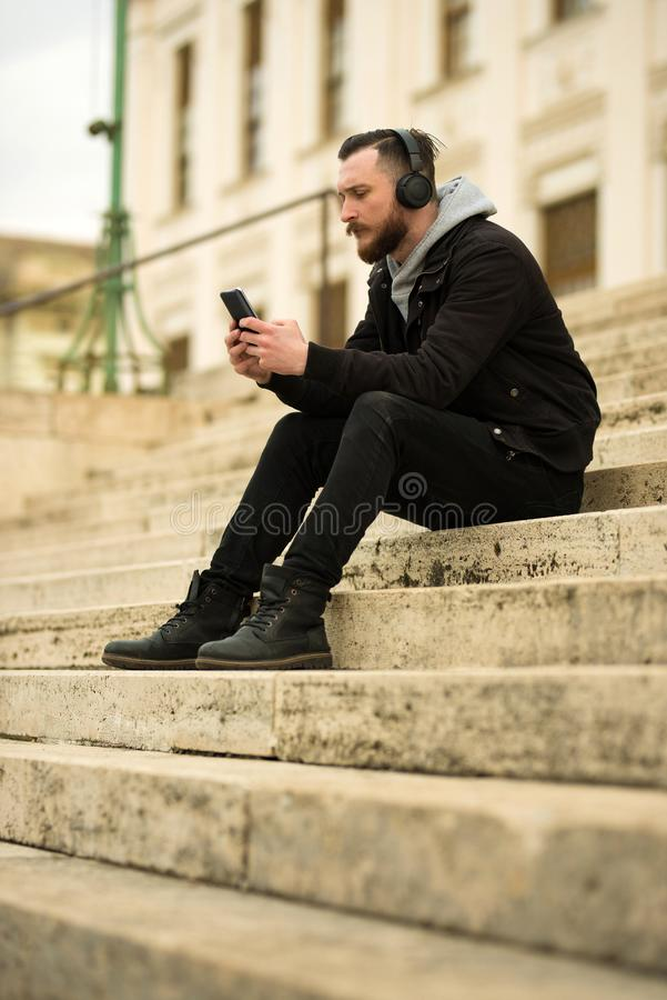 Hombre del inconformista en las escaleras con un smartphone fotografía de archivo