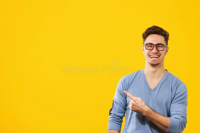 Hombre del inconformista en vidrios que señala feliz lejos en fondo del amarillo anaranjado fotos de archivo libres de regalías