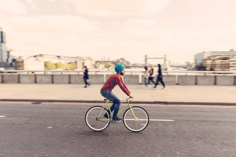 Hombre del inconformista que completa un ciclo en el puente de Londres con la bici fija del engranaje foto de archivo libre de regalías