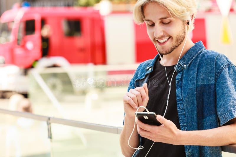 Hombre del inconformista que se coloca en música que escucha de la calle de la ciudad imagen de archivo