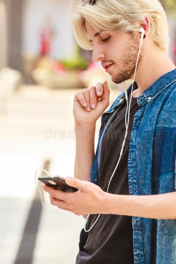 Hombre del inconformista que se coloca en m?sica que escucha de la calle de la ciudad foto de archivo libre de regalías