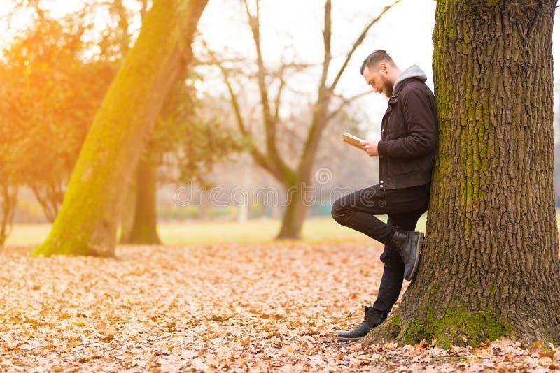 Hombre del inconformista que se inclina contra un árbol y una lectura imagenes de archivo