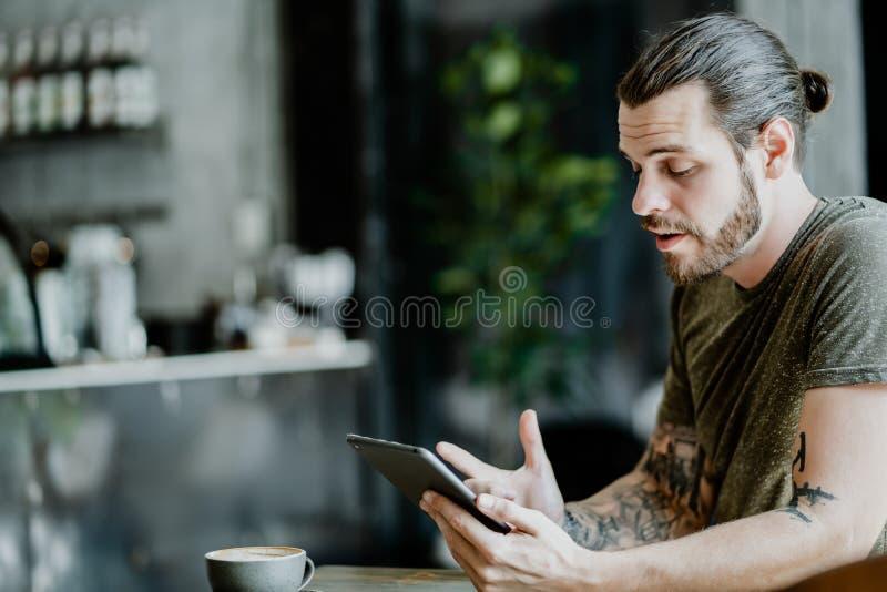 Hombre del inconformista usando la sonrisa de la tableta que se sienta en Internet que practica surf del café fotografía de archivo libre de regalías