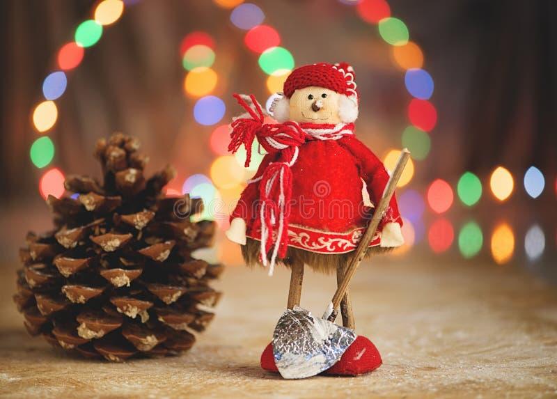 Hombre del juguete con la pala al lado del cono del pino Decoraciones de la Navidad imagen de archivo