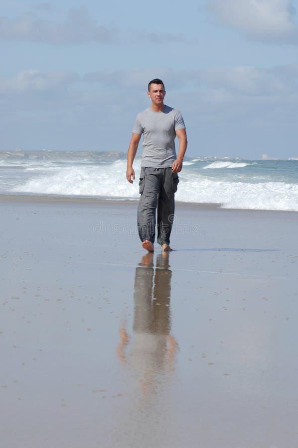 Hombre del Latino que recorre en una playa foto de archivo